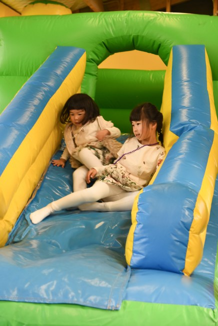 Two sisters playing in a slide in a playground for their birthday party