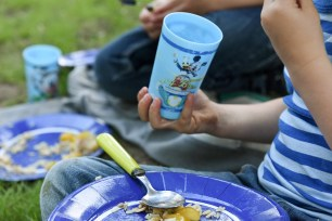 Blue plastic glass in the hand of a young boy for pic nic