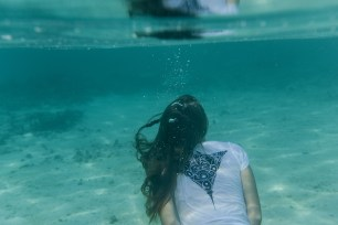 Woman wearing a Cloud 9 tee shirt under the ocean in Fiji by Anais Photography