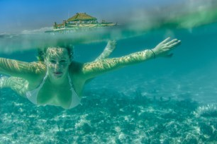 Over under shot with woman swimming toward the camera and Cloud 9 floating bar on the top in Fiji by Anais Photography