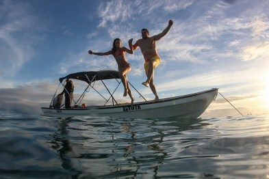 Couple jumping from the boat to the sea