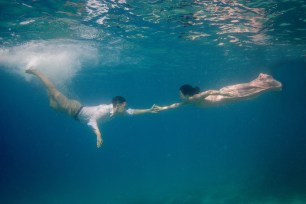 Couple reaching to each other underwater in Fiji