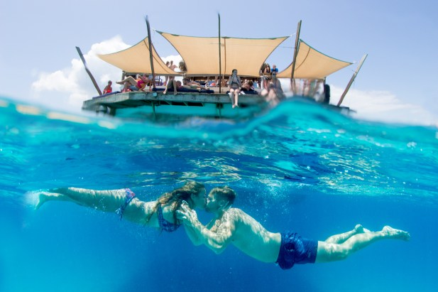 Over under shot with Cloud 9 bar on the top and couple kissing under the water in Fiji by Anais Photography