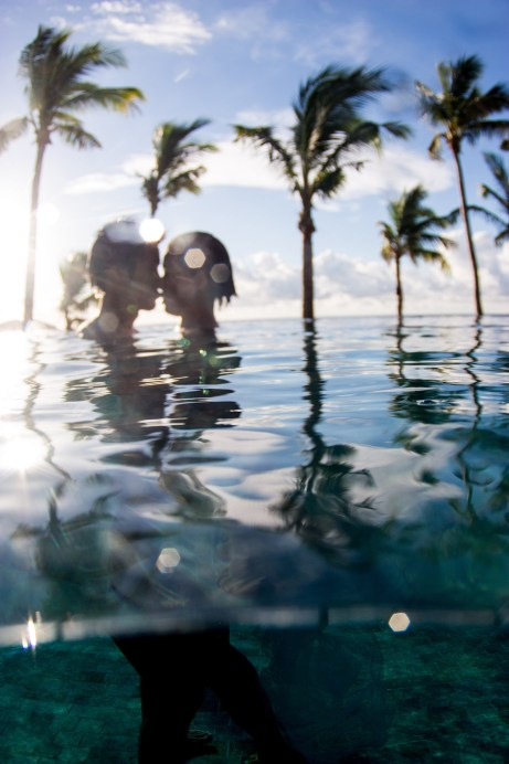 In Tokoriki island resort couple kissing with sun coming through and palm trees in Fiji by Anais Photography