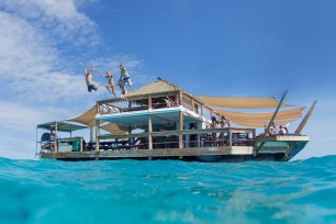 Friends jumping off the top of Cloud 9 in the Mamanuca islands in Fiji