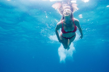 Reflection of a woman swimming underwater
