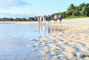3 generations of family stand on the Natadola beach in Fiji