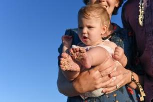 Baby with sandy feet carried against azure sky in Natadola beach Fiji