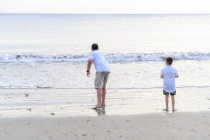 Father and son play on the beach in Natadola Fiji during sunset
