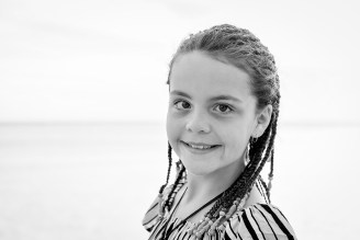 Black and white picture of cute young girl in braids on the beach