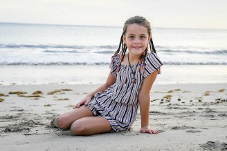 Cute young girl in braids seated on the beach in Fiji sunset