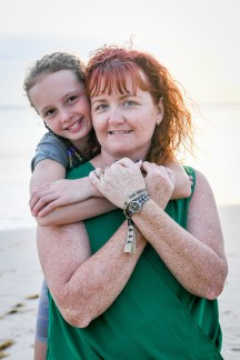 Braided daughter hugs neck of Red haired mum in Family beach photoshoot