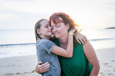 Braided daughter hugs red haired daughter on sunset