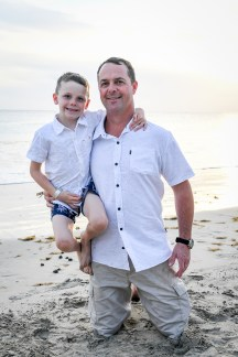 Father carries son in family beach photography in Natadola Fiji