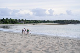 Wide shot of family strolling on beach in sunset in Fiji Natadola