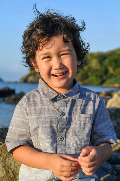 Cute curly haired boy laughs at the beach in family photo session