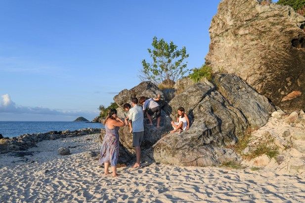 Cute family climb rocks on the sandy beach in Malolo Fiji