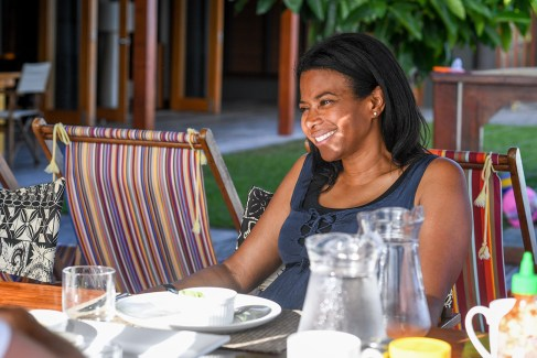 Polynesian mom smiles at breakfast table in family vacation in Fiji