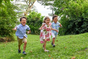 Triplets run on green lawn during Fiji family vacation