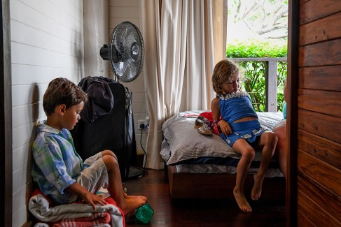 Triplets seated on the bed during family vacation Fiji