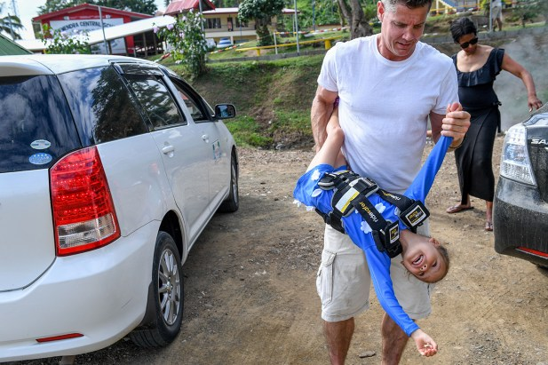 Dad carries daughter upside down during Fiji family vacation