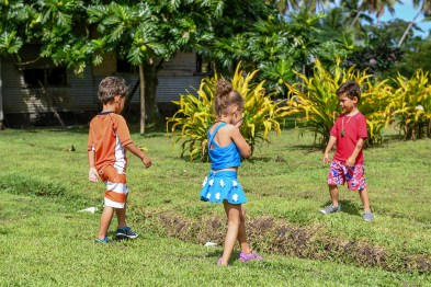 Triplets play in the grass in Fiji family vacation