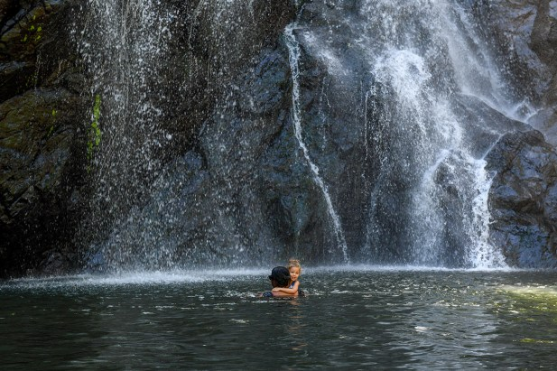 Dad and daughter swim in the river against waterfall in Fiji