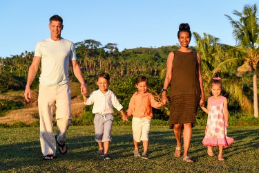 Family hold hands and walk towards the sunset in Fiji family photoshoot