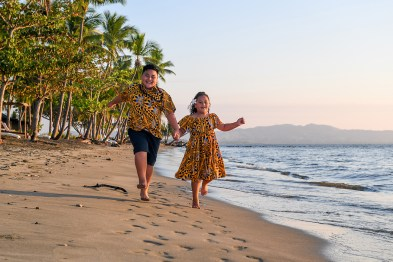 Brother and sister run and play along the shore at Double Tree Hilton Fiji