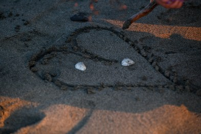 The family draws a simple love heart in the sand