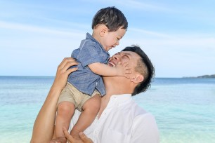 The father lifts his son above his head while in the turquoise blue waters