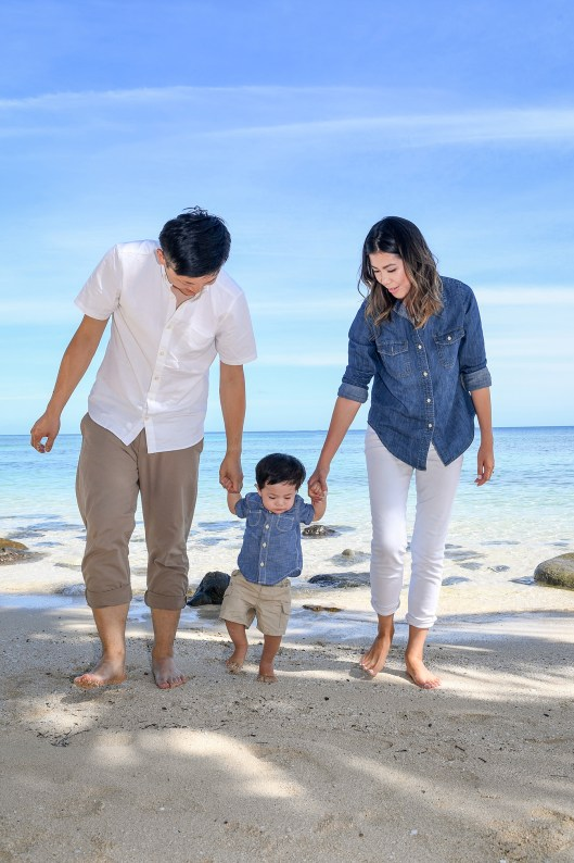 The cute baby boy takes his first steps on the beach at Plantation Island Resort