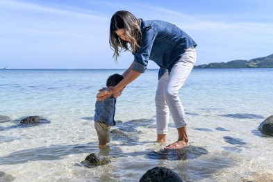 Mother helps her son take his steps on the clear waters at Plantation Island Resort