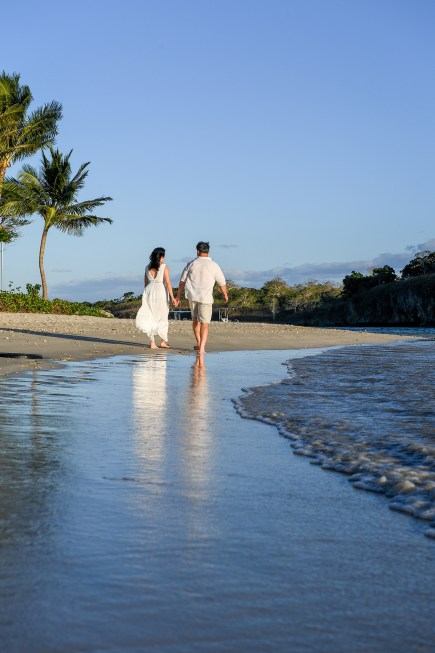 An asian couple strolls on the beach at Natadola Fiji