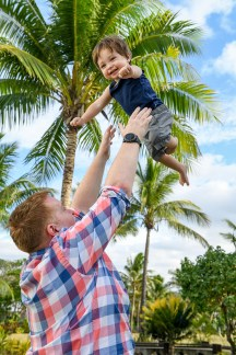 The baby is tossed up in the air against palm trees in Fiji