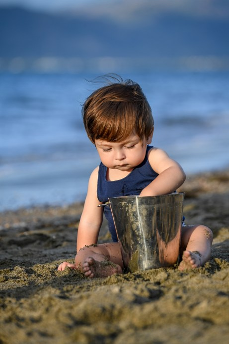 A baby plays around with sand in a bucket at the beach