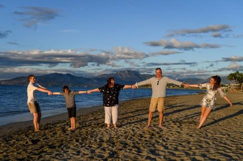 Family holds hands on the beach at Denarau Fiji