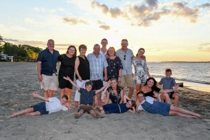 An extended caucasian family poses on the beach at Natadola