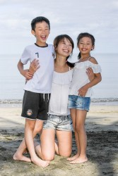 Cute asian family pose on the beach