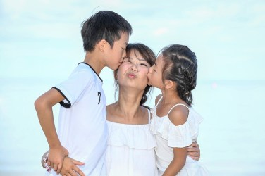 Asian daughter and son kiss their mother against baby blue sky