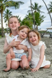 Sister, sister and brother in white cuddle against palm trees
