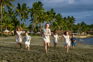 Cousins in white run on the beach against palm trees
