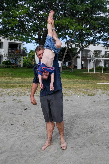 A father carries his son upside down