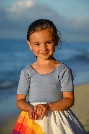 Cute girl in a rainbow dresses smiles at the camera