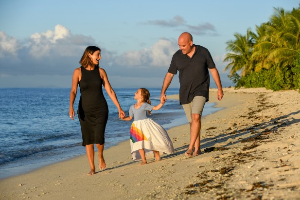 The cute family holds hands as they stroll on the beach