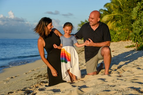 The family poses for photograph while kneeling in the sand