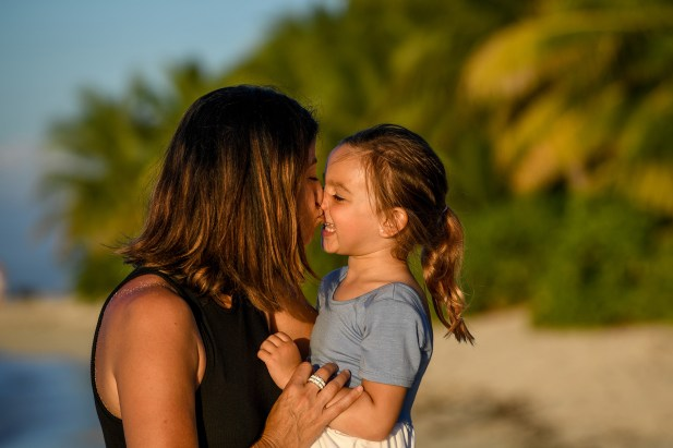 A mother kisses her daughter while on the beach