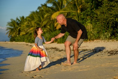 Father and daughter play games on the beach