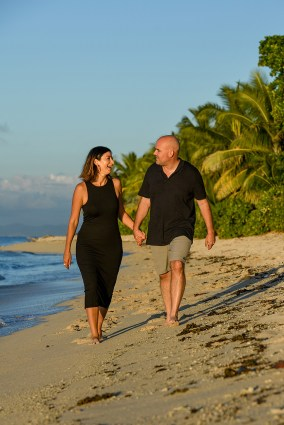 The couple dressed in black hold hands and stroll on the beach