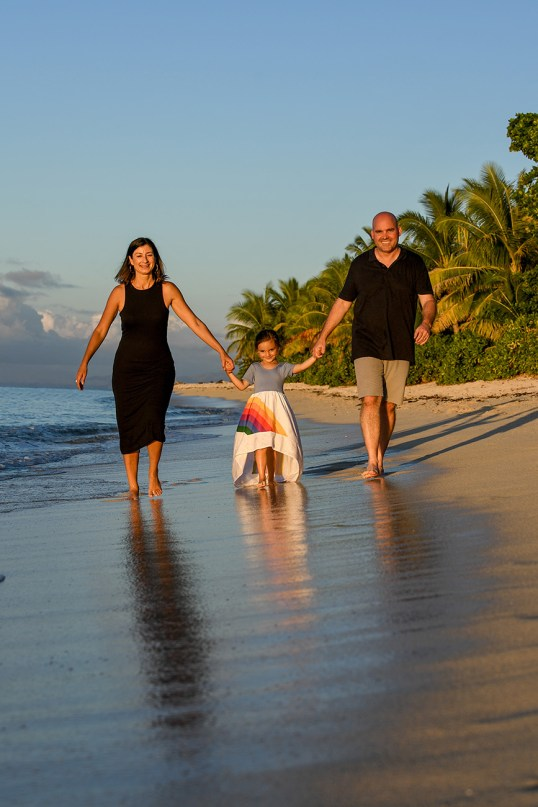 The sun kissed family hold hands as they wade in shallow waters at sunset